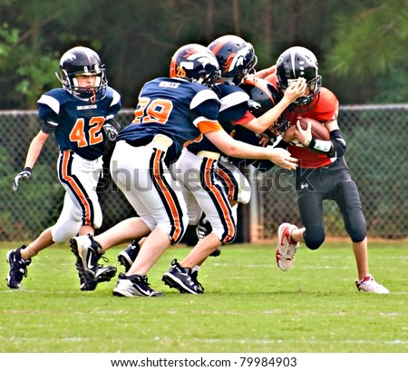 CUMMING, GA - SEPTEMBER 12: Unidentified players make a tackle during a Broncos vs.The Eagles recreational football game on September 12, 2009 in Forsyth County, Cumming, GA. The game is part of the local Recreation Department Football Program. - stock photo