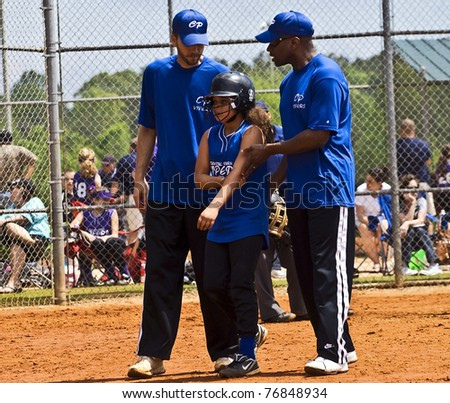 CUMMING, GA, USA - APRIL 23: Young unidentified baseball player being taken care of by coaches after an injury. April 23, 2011, Forsyth County, Cumming, GA; the Coyotes vs the Vipers. - stock photo