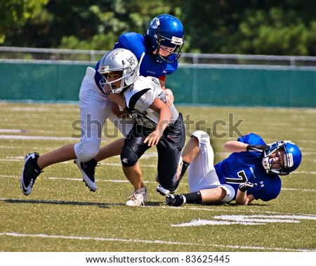 CUMMING, GA, USA - AUGUST 27 : 11 to 13-year-old unidentified boys running and tackling during a football game, the Raiders vs the War Eagles, on August 27, 2011 in Cumming GA. - stock photo