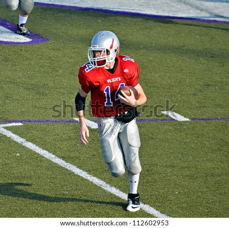 CUMMING, GA/USA - SEPTEMBER 8: Unidentified boy running with the ball . Two teams of 7th grade boys September 8, 2012 in Cumming GA. The Wildcats  vs The Mustangs. - stock photo