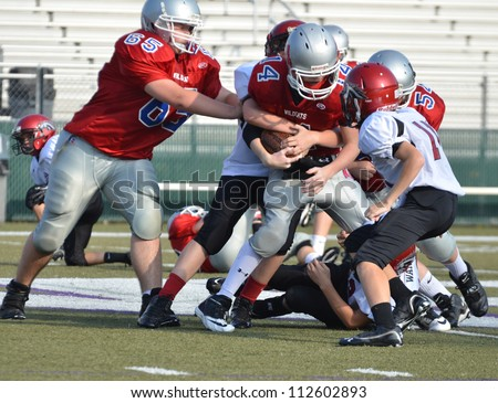 CUMMING, GA/USA - SEPTEMBER 8: Unidentified boys blocking and tackling during a football game. Two teams of 7th grade boys September 8, 2012 in Cumming GA. The Wildcats vs The Mustangs. - stock photo