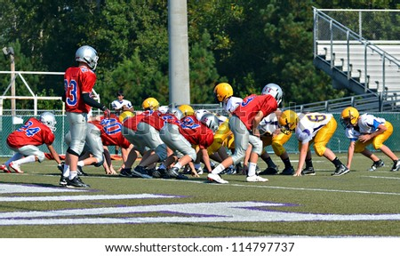 CUMMING, GA/USA - SEPTEMBER 22: Unidentified players at the line during a football game of 7th grade boys September 22, 2012 in Cumming GA.  North Forsyth vs Lakeside. - stock photo