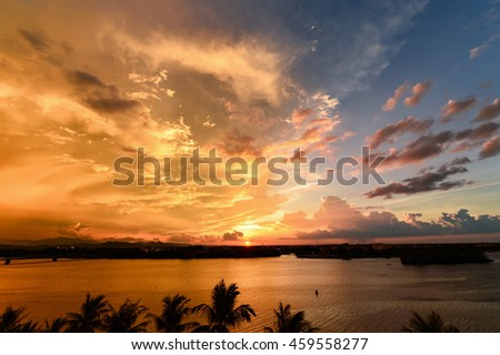 Cumulus sunset clouds with sun setting down - stock photo