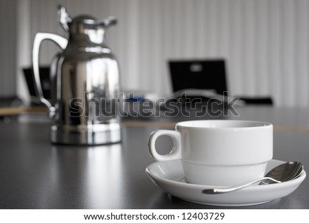Cup and Coffee Pot on Desktop - stock photo