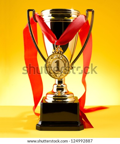 cup and medal on a yellow background - stock photo