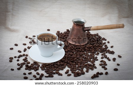 Cup and pot of coffee and coffee beans on beige background - stock photo
