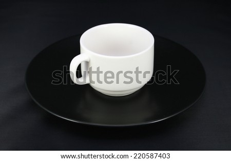 Cup and saucer on black background - stock photo