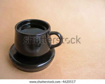 Cup and saucer on brown background - stock photo