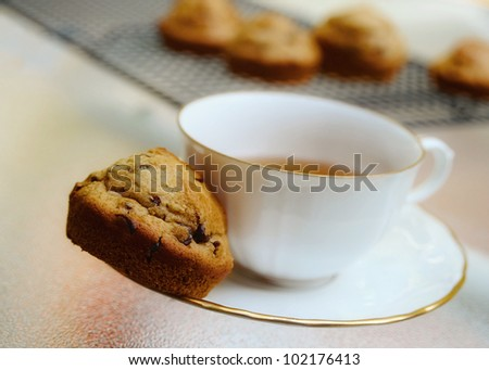Cup and saucer with muffin on plate with muffins on cooling rack in background. - stock photo