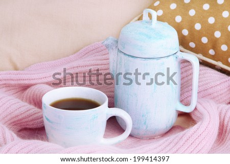 Cup and teapot with scarf on bed close up - stock photo
