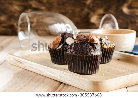 cup cake topping with chocolate wafer on wooden - stock photo