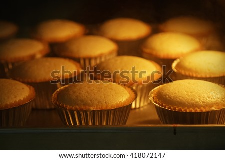 Cup cakes baking in oven, homemade bakery - stock photo