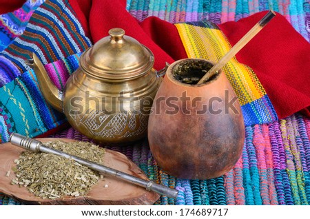 Cup from calabash and teapot with dry mate leaves.Traditional drink of Peru, Brazil and Argentina.  - stock photo