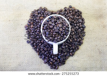 Cup full of coffee beans and heart shape on burlap hessian sacking texture background - stock photo