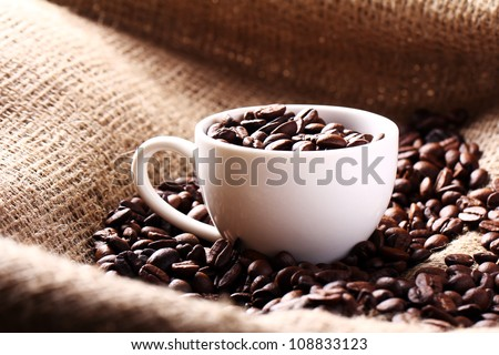 Cup full of coffee beans on the cloth sack - stock photo