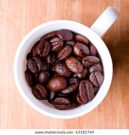cup full of coffee beans on wooden background - stock photo