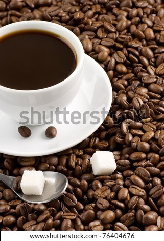 cup full of coffee, spoon and beans - stock photo