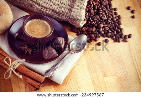 Cup hot coffee with beans and chocolate candies instagram styled vintage retro photo - stock photo