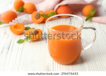 Cup of apricot juice and fresh fruits on table close up - stock photo