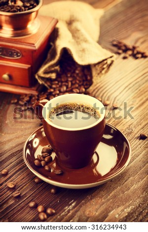 Cup of aromatic coffee on saucer. Cup of coffee with coffee ginger and burlap sack full of roasted coffee beans over wooden table. Vintage style. Vertical photo  - stock photo