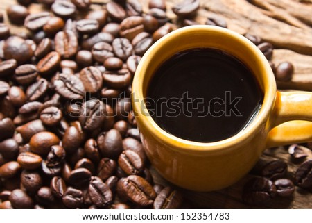 Cup of black coffee and coffee beans on  wooden background. - stock photo