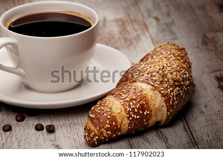 cup of black coffee and croissant over grunge wood - stock photo