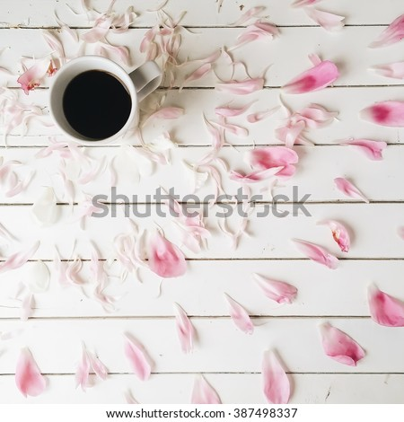 Cup of black coffee and pink peony petals on white wooden background. Overhead view. Flat lay, top view - stock photo