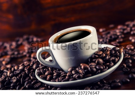 Cup of black coffee and spilled coffee beans. Coffee break - stock photo