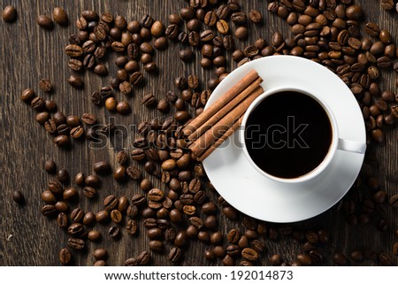 cup of black coffee with cinnamon sticks and coffee beans around - stock photo