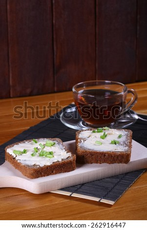 Cup of black tea and sandwiches on the table. Transparent cup of tea. Two sandwiches with butter or cream cheese and chives. Snack, breakfast, lunch. - stock photo