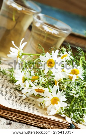 cup of black tea, wild chamomile, old books on wood background, selective focus - stock photo