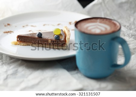 Cup of cacao and a piece of cake. Latte art.  - stock photo