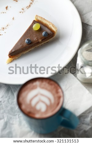 Cup of cacao and a piece of cake. Latte art. Top view - stock photo