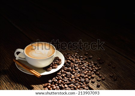 Cup of cafe latte and coffee beans on old wooden background - stock photo