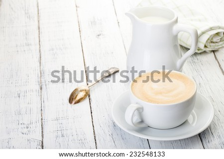 cup of cappuccino and jug of milk on old painted white wooden table. - stock photo