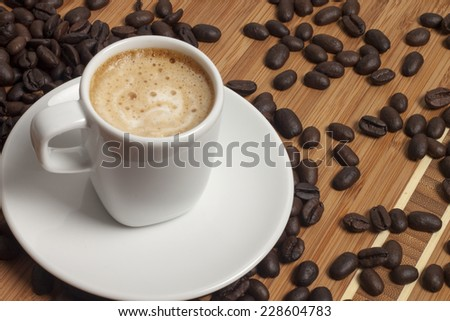 Cup of cappuccino and spilled out coffee beans.  - stock photo