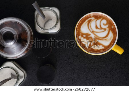 Cup of cappuccino and sugar bowls on black background. Latte art. Top view - stock photo