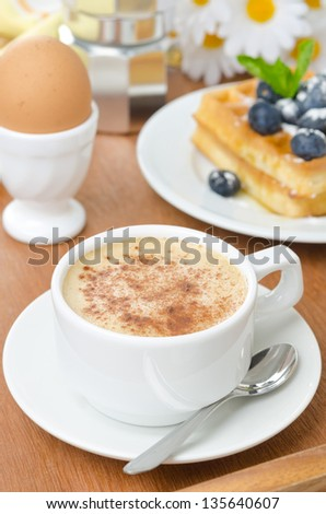 cup of cappuccino, belgian waffles with blueberries and egg for breakfast closeup - stock photo