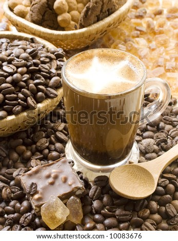 Cup of cappuccino coffee with cinnamon powder, surrounded by coffee beans, cookies, crystallized brown sugar and chocolate. - stock photo