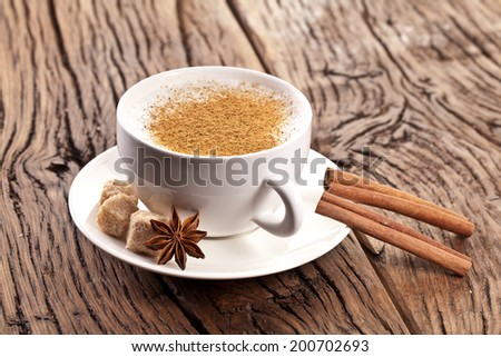 Cup of cappuccino decorated with spices and cubes of brown sugar near it. - stock photo