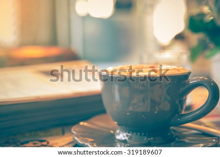 Cup of cappuccino in the coffee shop with magazine, vintage tone - stock photo