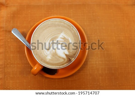 Cup of cappuccino on a tablecloth in the cafe - stock photo