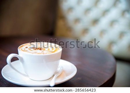 Cup of cappuccino on the table, coffee shop background - stock photo
