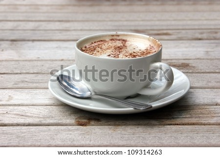 Cup of Cappuccino on wooden slat table with chocolate - stock photo