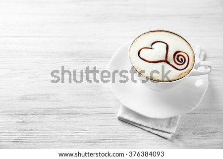 Cup of cappuccino with chocolate syrup on light wooden table - stock photo