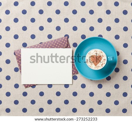 Cup of cappuccino with heart shape and envelope on polka dot background. - stock photo