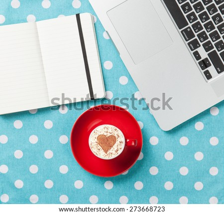 Cup of cappuccino with heart shape and laptop with note on blue polka dot background. - stock photo