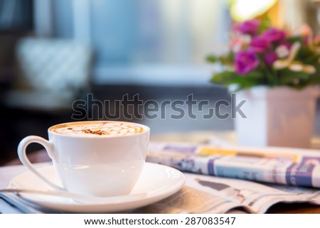 Cup of cappuccino with newspaper in coffee shop  - stock photo