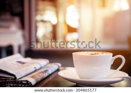 Cup of cappuccino with newspaper on the table, coffee shop background, warm tone - stock photo