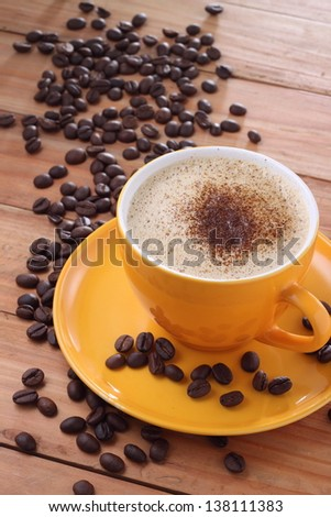Cup of cofee with coffee beans on a wood table - stock photo